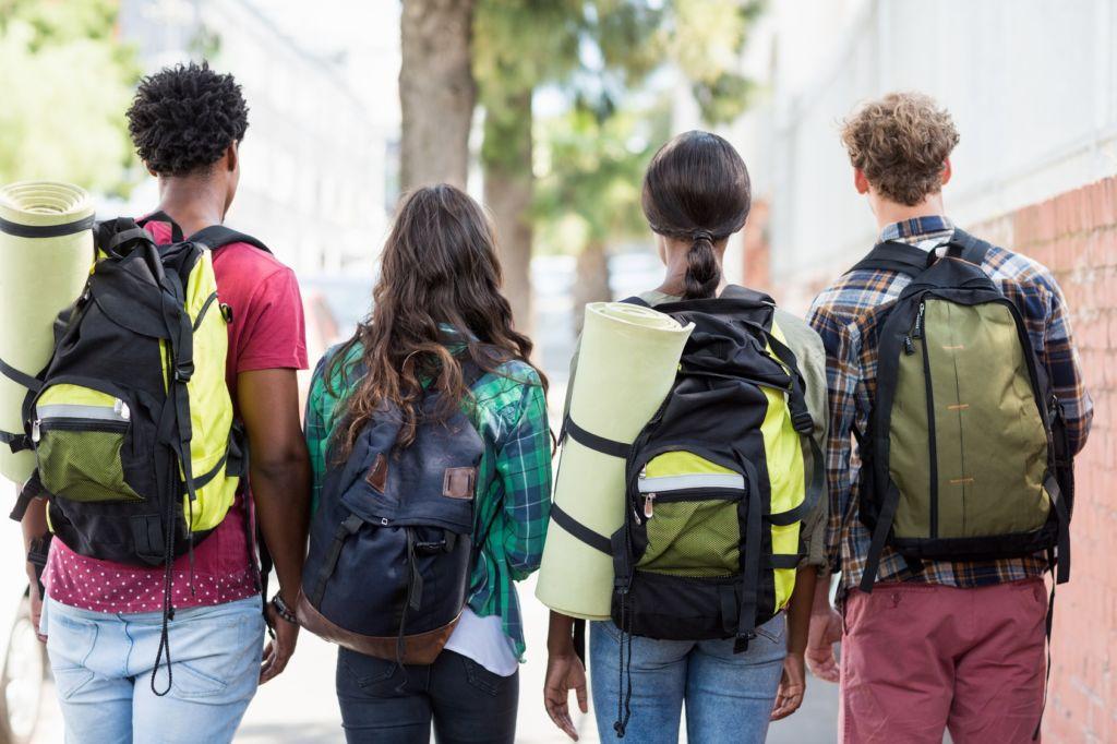 4 niños de espaldas con la mochila a cuestas