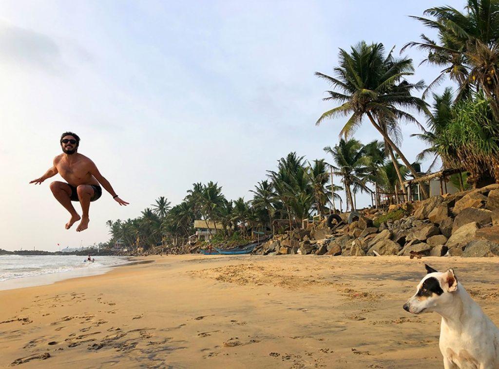Hombre saltando en una playa en Sri Lanka con un perro