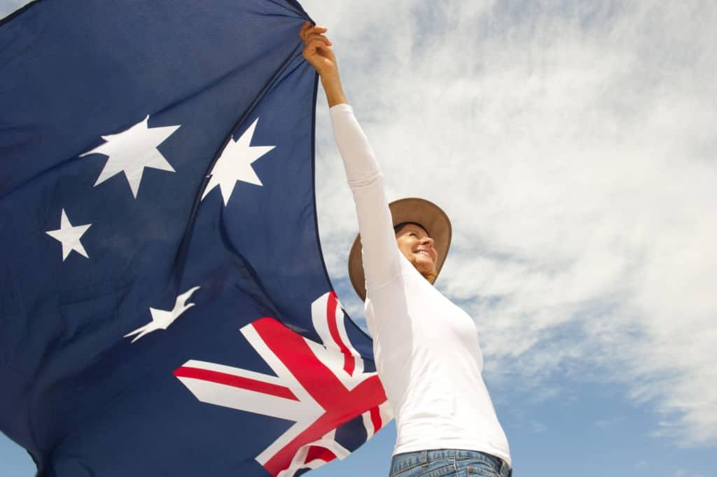 Mujer con la bandera de Australia y el cielo de fondo