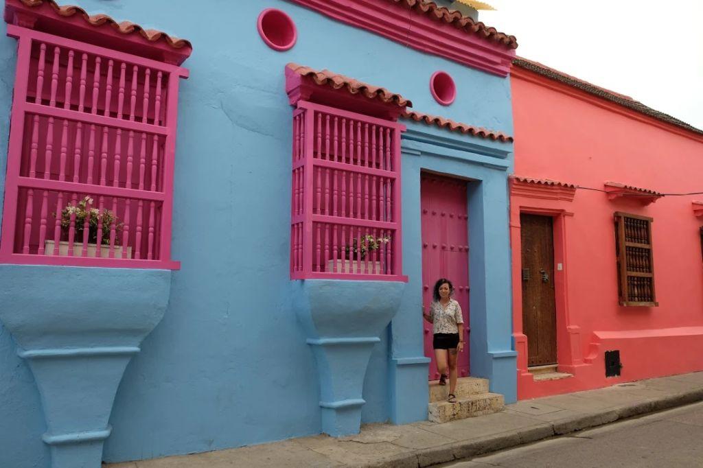 Mujer en la puerta de una casa colorida en Cartagena, Colombia