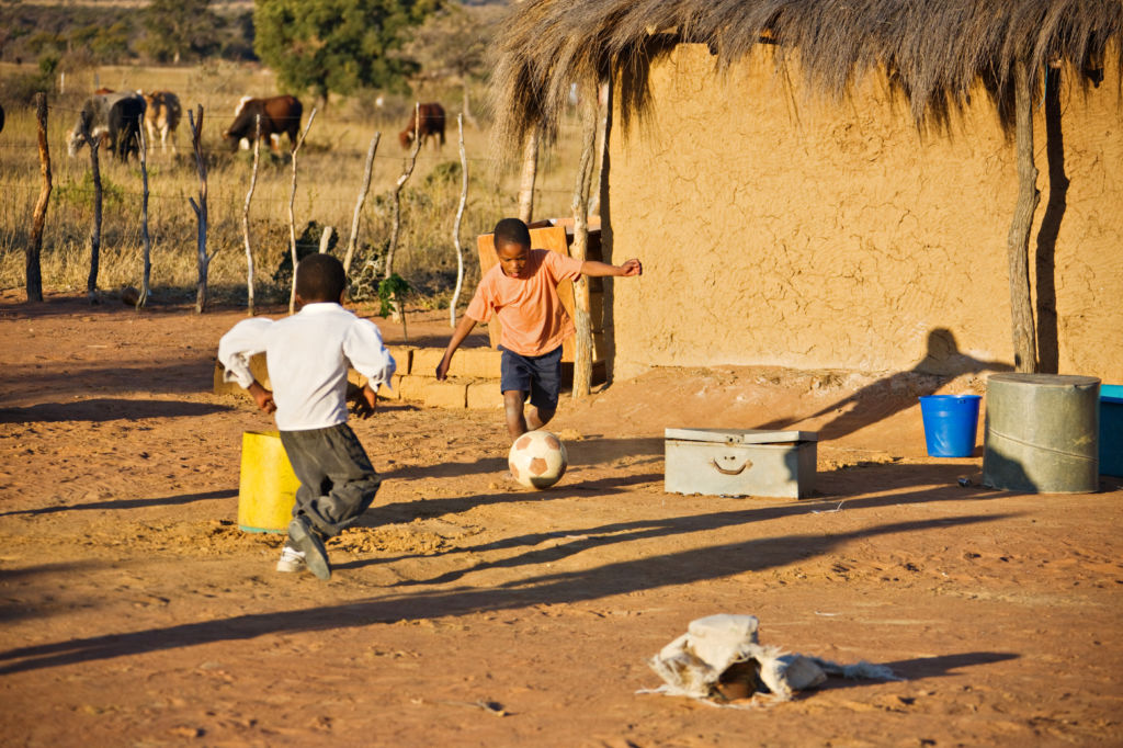 Niños jugando en el patio de una casa al fútbol