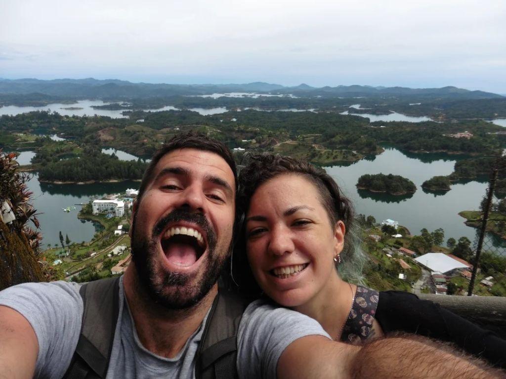 Pareja sonriendo con el Peñón de Guatapé detrás en Colombia