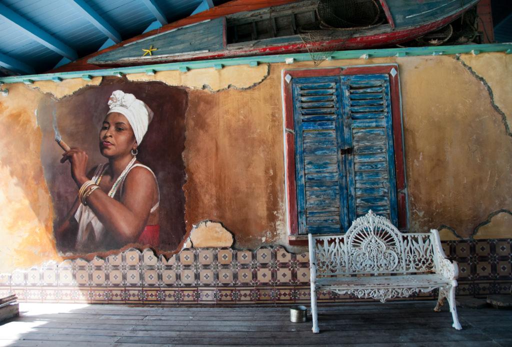 Banco blanco al lado de una casa con una fachada viaja en la que hay un mural de una mujer cubana fumando un puro