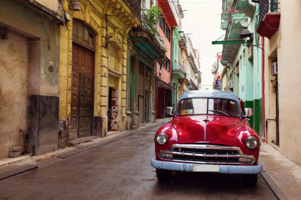 Coche rojo clásico en las calles coloridas de La Habana, en Cuba