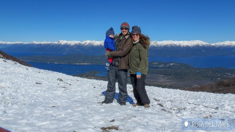 Familia en un paisaje nevado con montañas al fondo en Villa La Angostura, Argentina