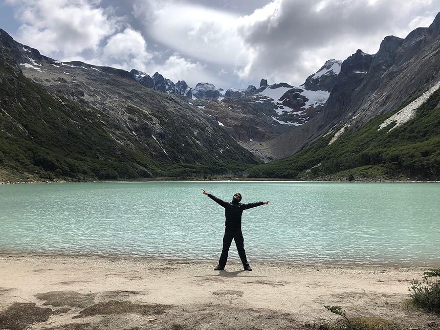 Hombre con los brazos abiertos delante de la laguna esmeralda en la Patagonia argentina