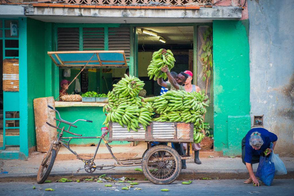 Hombre con un carro lleno de bananas verdes en las calles de La Habana en Cuba