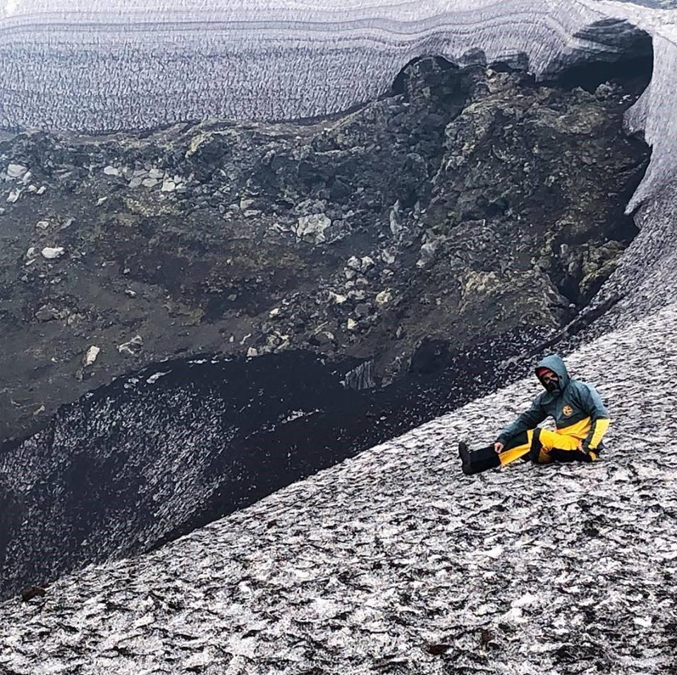 Hombre sentado al lado del cráter de Pucón en Argentina