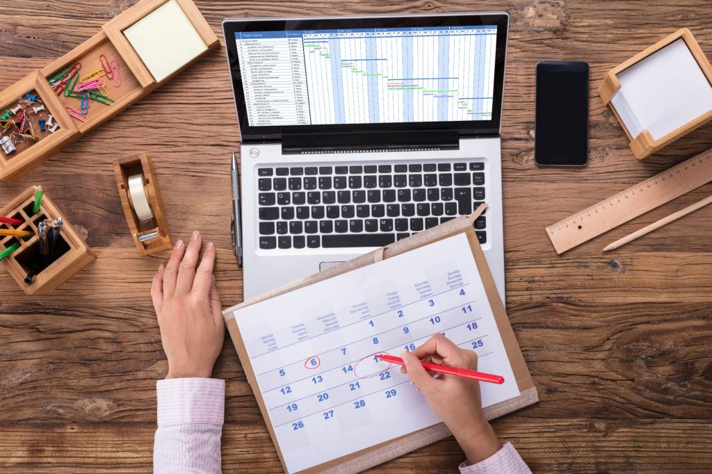 Manos señalando una fecha en un calendario encima de un ordenador