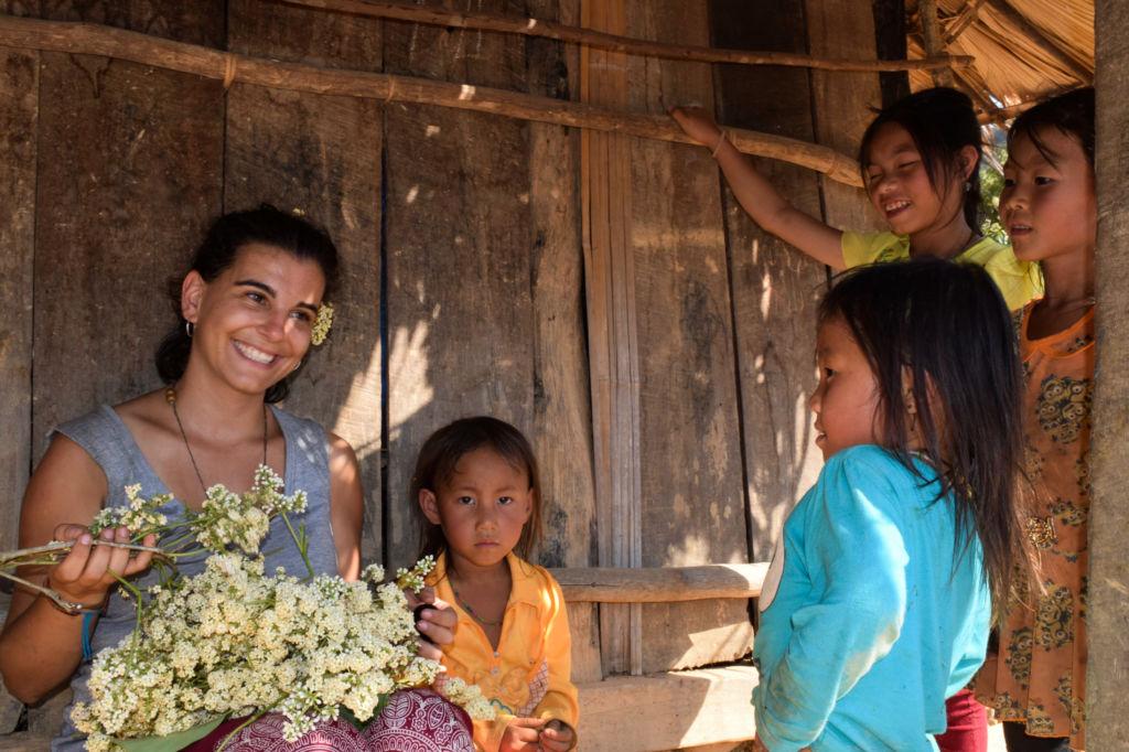 Mujer con flores en la mano y rodeada de niños en una cabaña en Laos