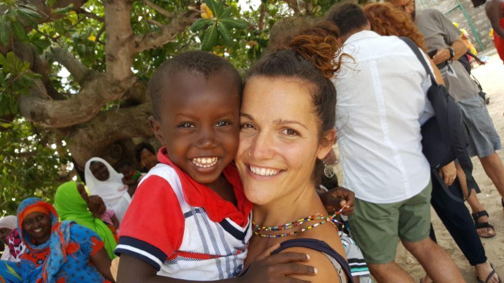 Mujer con niño africano en los brazos, sonriendo ambos