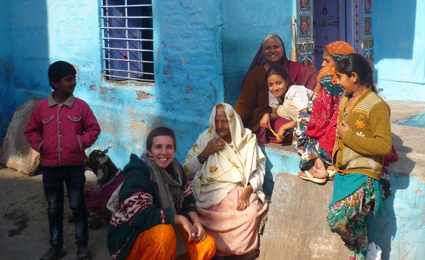 Mujer occidental con el pelo corto rodeada de mujeres indias en sari en el portal de una casa en India