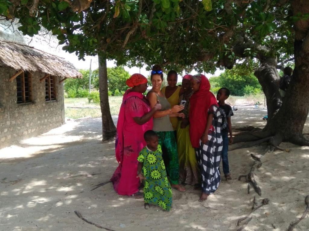 Mujer occidental rodeada de mujeres africanas en un patio exterior y bajo un árbol