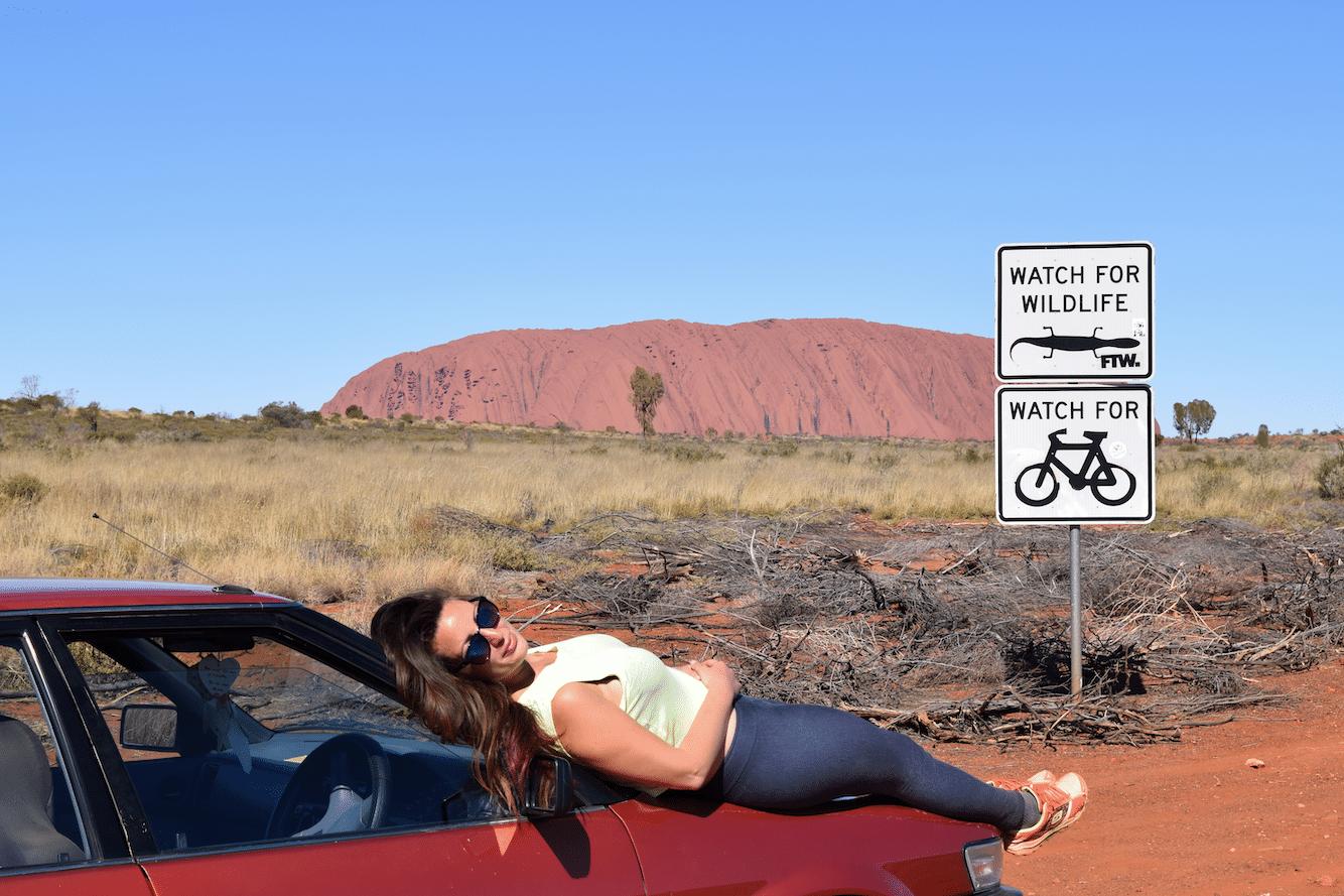 Mujer recostada encima de su coche en una carretera salvaje de Australia