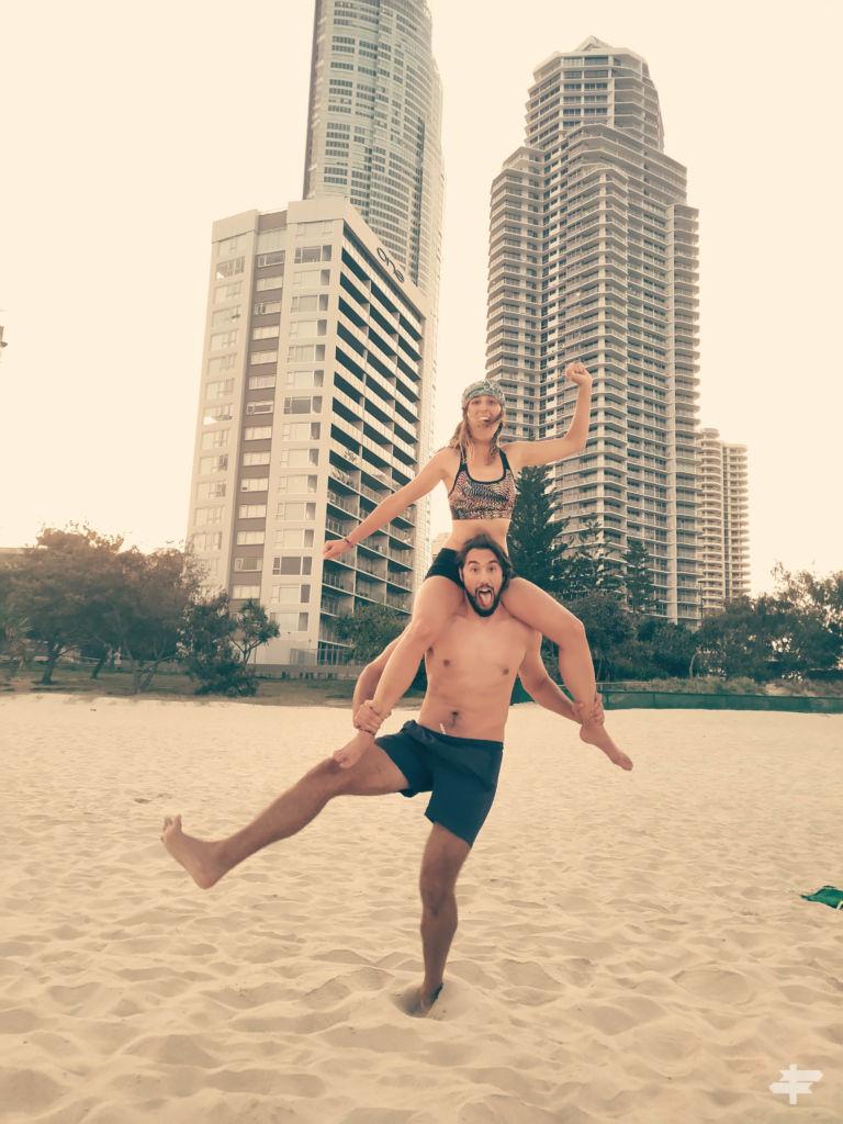 Mujer subida encima de un hombre en la playa con los edificios de Gold Coast, en Australia, de fondo