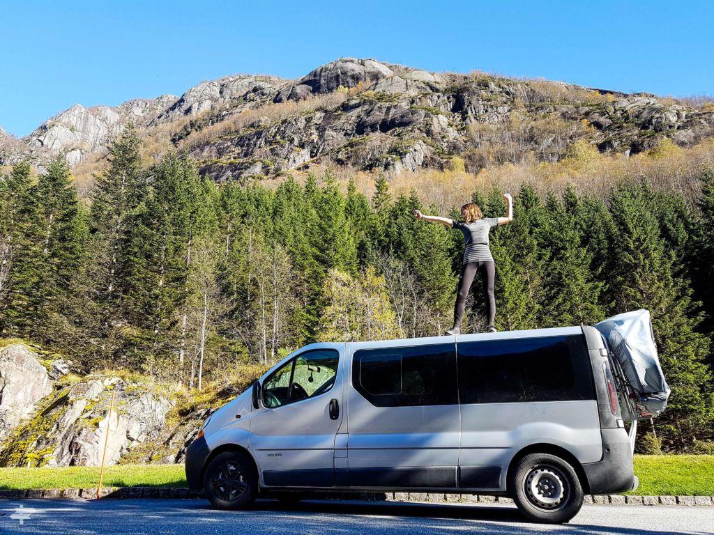 Mujer subida encima de una furgoneta con árboles y una montaña de fondo, en Noruega