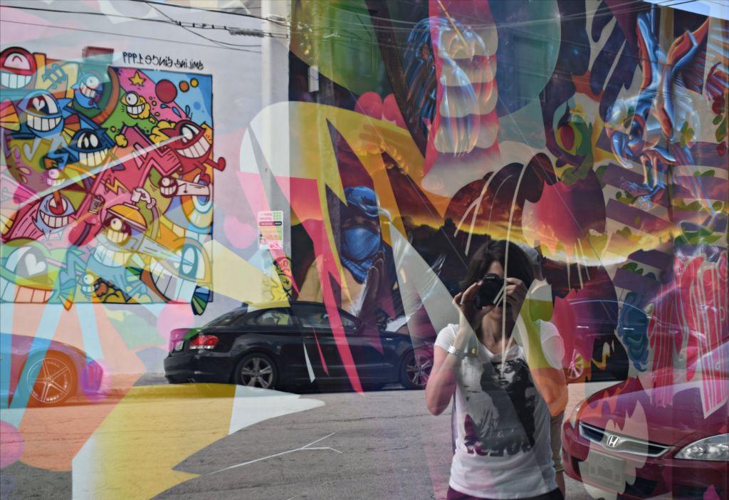 Reflejo sobre una vitrina colorida de una mujer con una cámara de fotos tapándole la cara