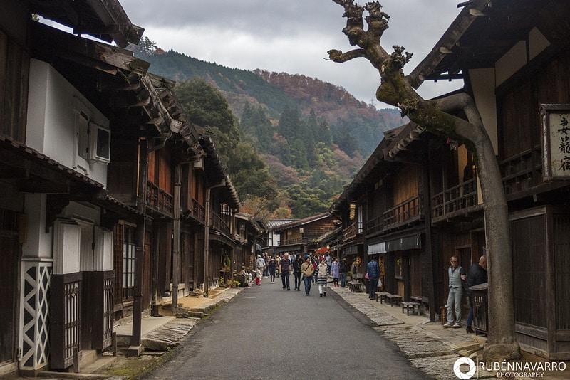 Vistas de una calle con casas tradicionales y una montaña de fondo e n la ruta Nakasendo en Japón