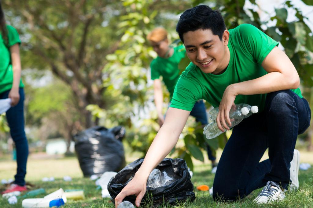 Voluntario recogiendo botellas en un parque