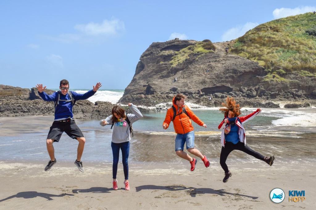Grupo de gente saltando en una playa de Nueva Zelanda