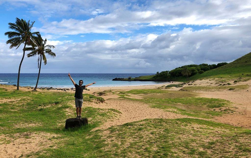 Hombre con los brazos levantados en la playa de Anakena en la Isla de Pascua