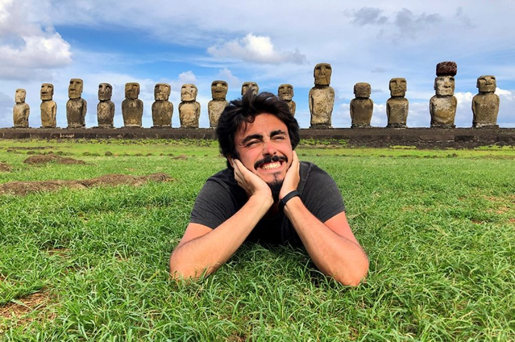 Hombre sobre el césped con las estatuas de la Isla de Pascua detrás