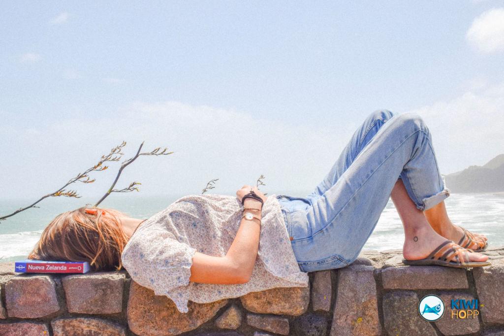 Mujer tumbada en un muro al lado de la playa