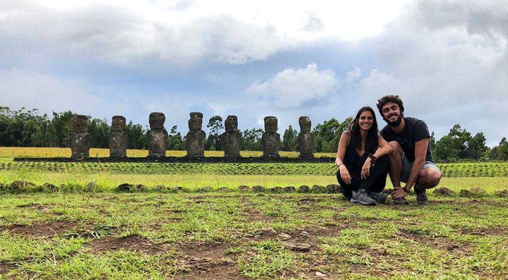 Pareja de hombre y mujer delante de 7 moais en Ahu Akivi en la Isla de Pascua