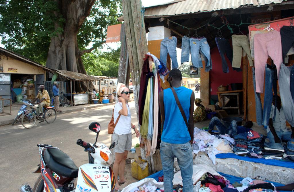 chica europea en mercado en Senegal hablando con Africano