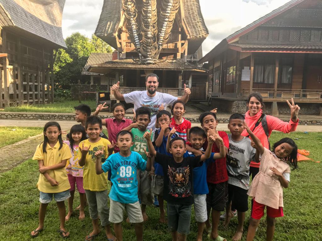 Grupo de niños con un hombre saludando en Raja Ampat en Indonesia