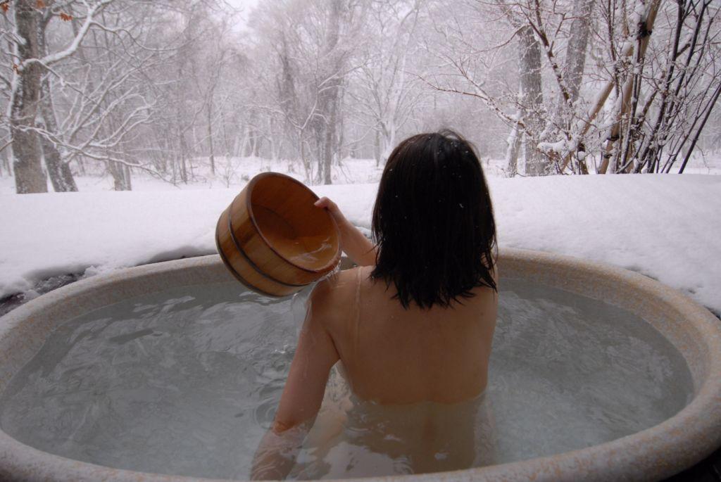 Mujer de espaldas echándose agua en un baño en un onsen japonés