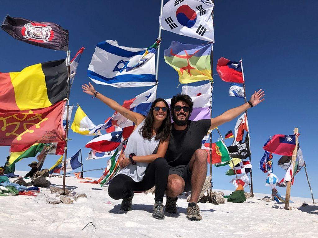 Pareja feliz con banderas en el Salar de Uyini Bolivia