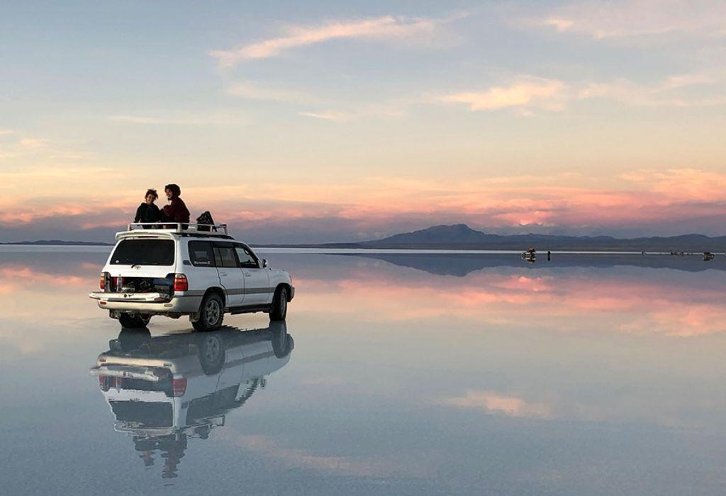 Pareja viendo el atardecer del Salar de Uyini en Bolivia en el techo del coche
