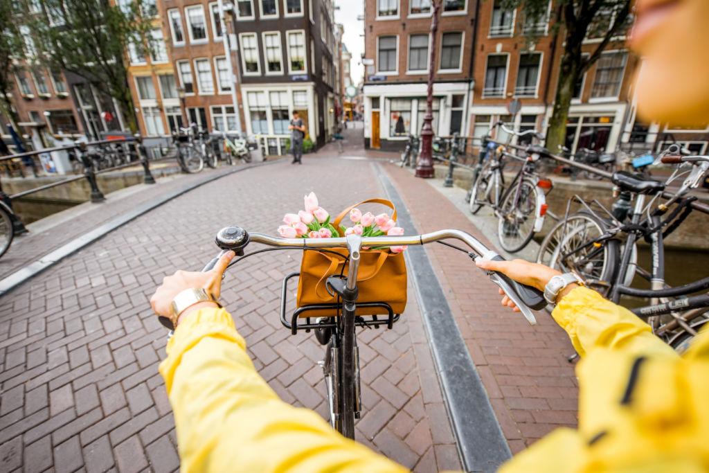 Vista frontal desde la bicicleta de un canal en Amsterdam