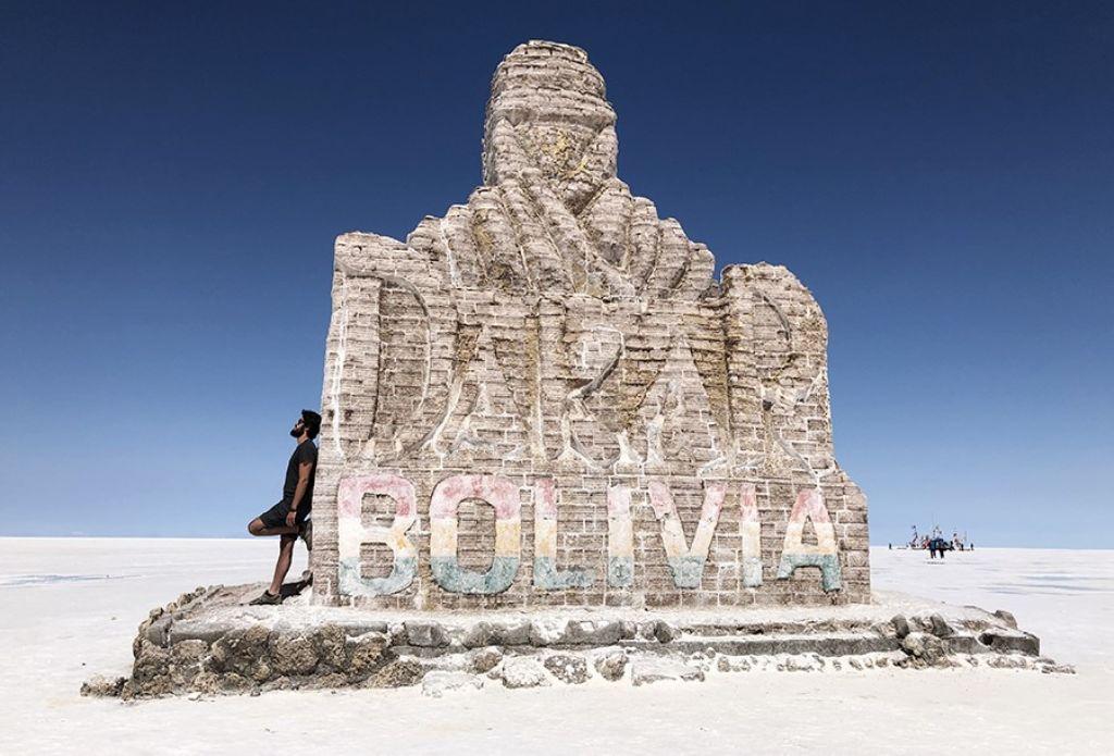 chico apoyado en la escultura del Dakar de Bolivia en el Salar de Uyuni