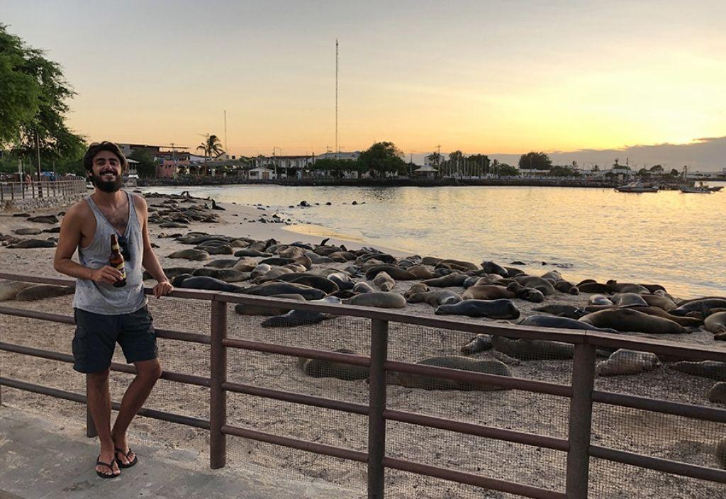 chico con cerveza en la playa en las islas Galápagos