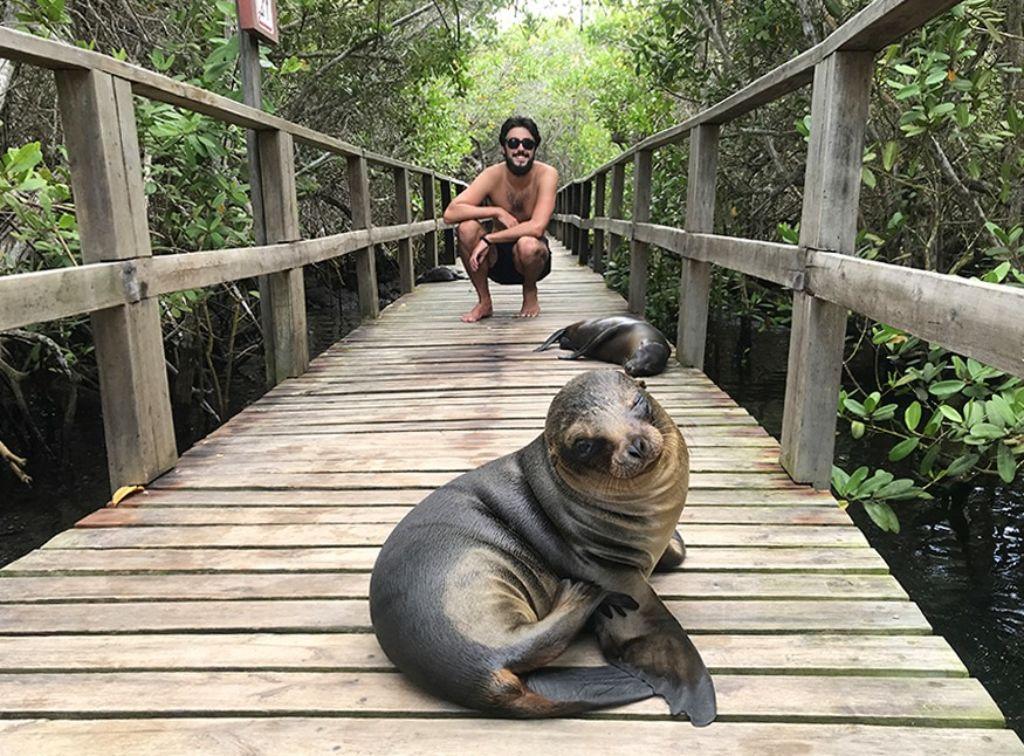 chico con leon marino en las islas galapagos