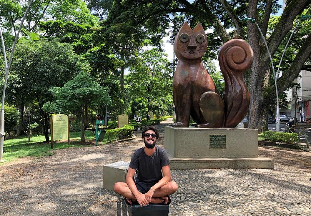 chico en Cali con estatua gato