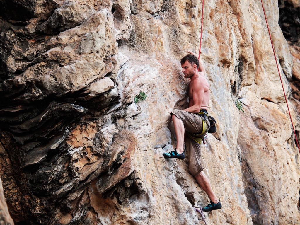 chico fuerte escalando una montaña en Tonsai, Tailandia