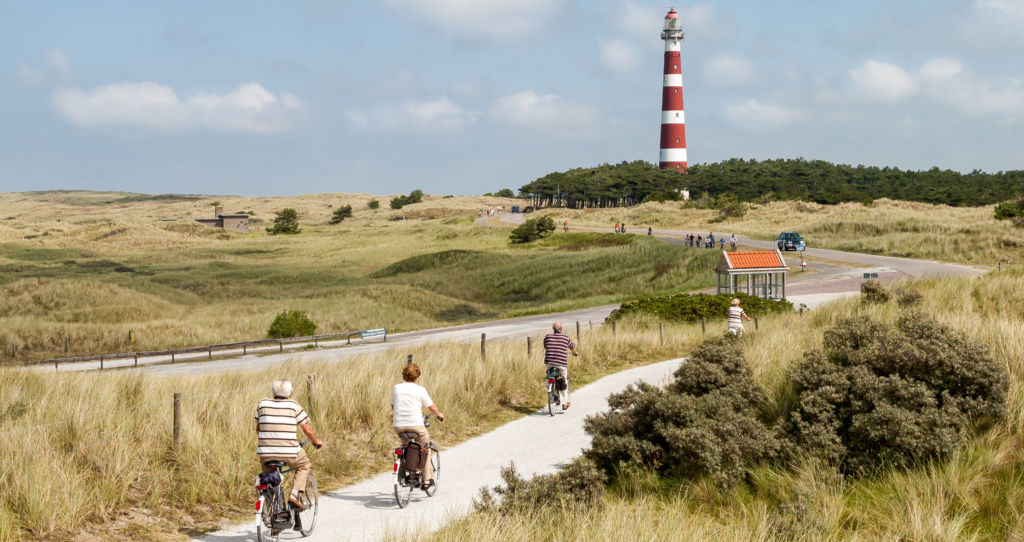 ancianos haciendo bicicleta en Ameland cerca de un faro en Holanda eurovelo