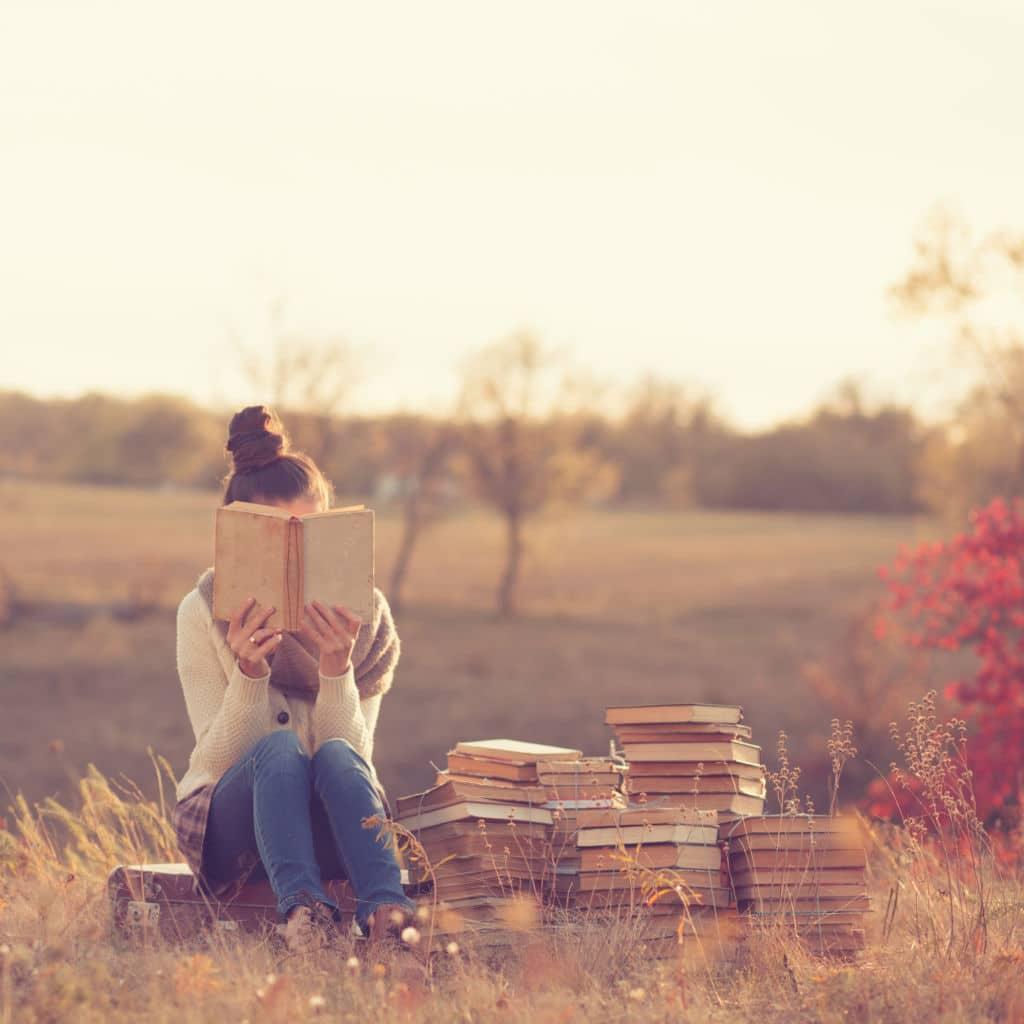 chica con muchos libros leyendo campo Tsundoku palabras sin traducción