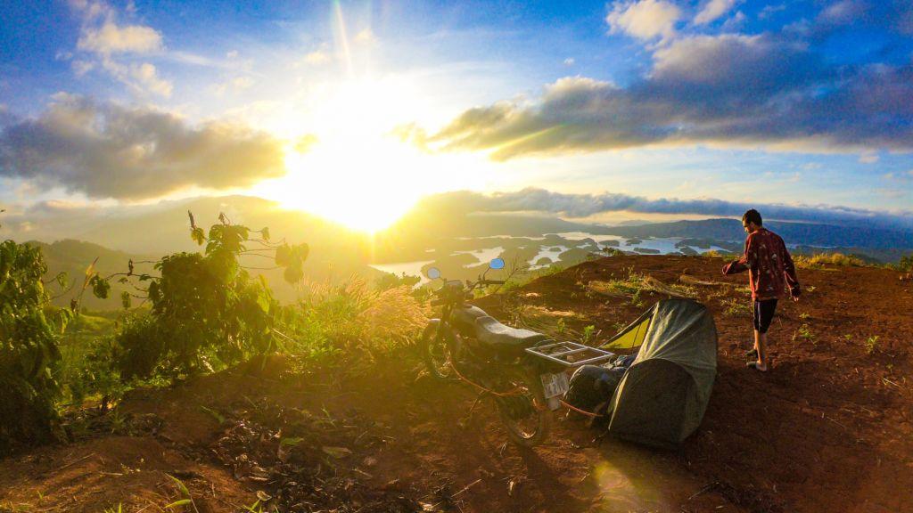 chico acampando mochilero puesta de sol