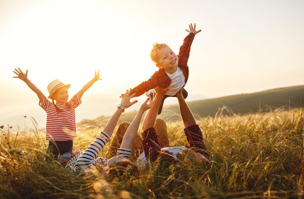 padres levantando a su hijo avión viajar vuelta al mundo en familia