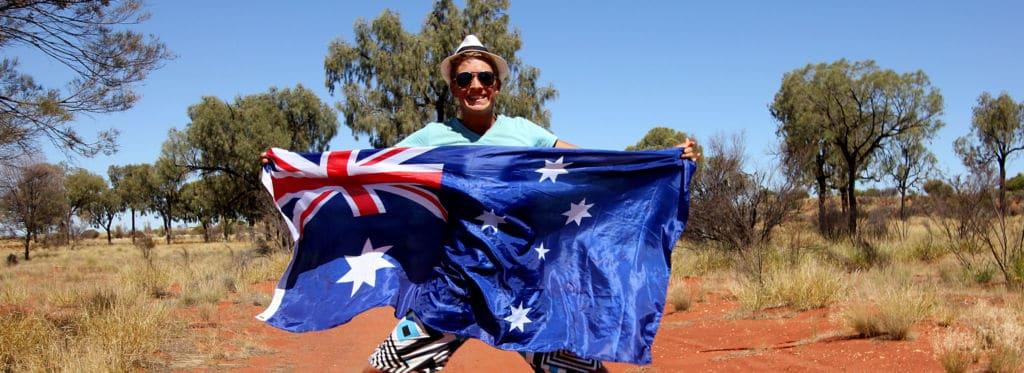 chico sosteniendo la bandera de Australia estudiantes fronteras covid19 working holiday visa nueva zelanda australia